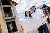 Couple holding blueprints — Stock Photo