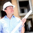 Thoughtful architect holding blueprints - Stock Photo