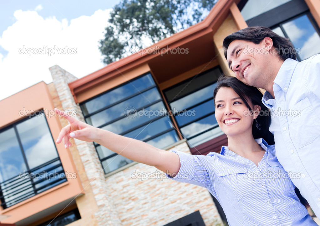 Happy couple pointing away in front of their home  — Stock Photo #13495795
