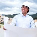 Thoughtful architect holding blueprints — Stock Photo