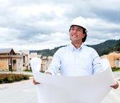 Pensive man holding blueprints — Stock Photo