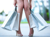 Tired woman holding shopping bags — Stock Photo