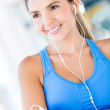 Woman with headphones at the gym - Stock Photo