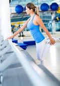 Kobieta siłownią rozciąga jej nogi — Zdjęcie stockowe