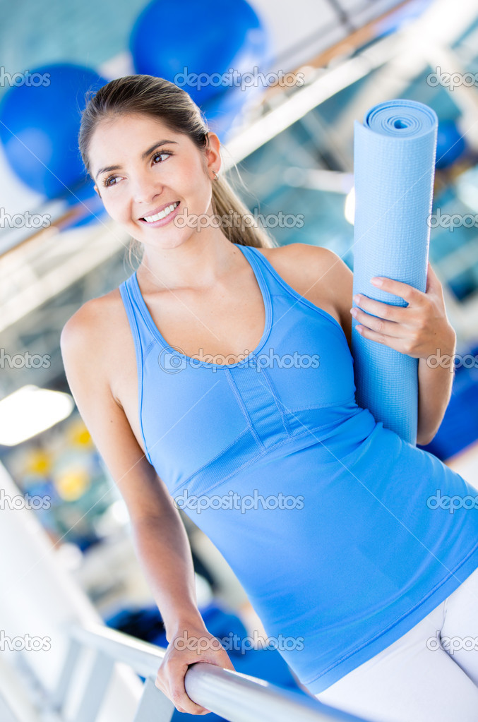 Beautiful woman with a yoga mat at the gym  — Stock Photo #14887895