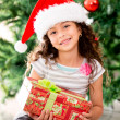 Girl holding a Christmas gift — Stock Photo