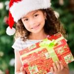 Christmas girl holding a present — Stock Photo #15064461