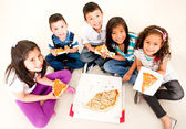 Group of kids eating pizza — Stok fotoğraf