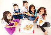 Skupina děti jedí pizzu — Stock fotografie