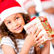 Adorable girl holding a Christmas present - Stockfoto