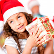 Pensive girl with a Christmas gift — Stock Photo #15659627