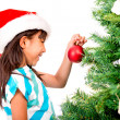 Girl decorating the Christmas tree - Stock Photo