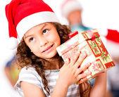 Fundersam tjej med en julklapp — Stockfoto