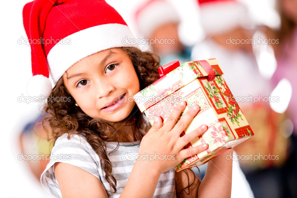 Adorable girl holding Christmas present and wearing Santa's hat  — Stock Photo #15659621
