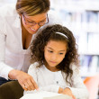Schoolgirl reading with her teacher — Stock Photo