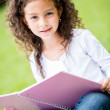 Cute schoolgirl at the park — Stock Photo