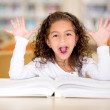 Stock Photo: Excited girl reading a book