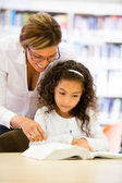 Schoolgirl reading with her teacher — Foto Stock