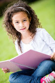 Cute schoolgirl at the park — Stock Photo