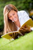 Woman reading outdoors — ストック写真