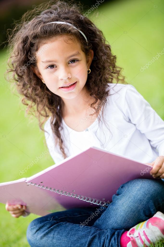 可爱小女生在公园举行一个笔记本