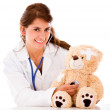 Doctor fixing a sick teddy bear Doctor fixing a sick teddy bear - Stock Photo