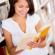 Stock Photo: Female student reading book Female student reading book