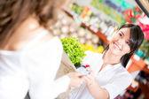 Femme accordant à la femme de supermarché payer au supermarché — Photo