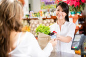Mujer a la mujer de compras de pago de compras en la caja — Foto de Stock