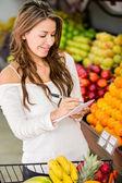 Femme avec une femme commerçante de liste avec une liste de courses — Photo