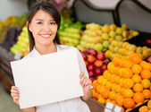 Female holding a banner at the supermarket Female holding a banner at the supermarket — Stock Photo