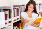 Estudiante en el estudiante femenino de biblioteca en la biblioteca — Foto de Stock