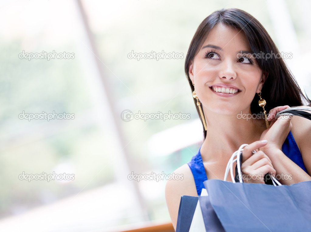 Thoughtful shopping woman holding bags and smiling Thoughtful shopping woman holding bags and smiling  — Stock Photo #16963153