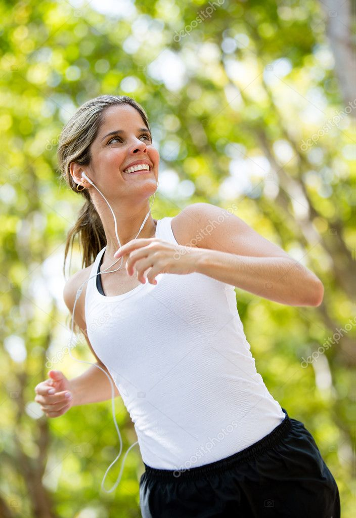 woman jogging outdoors looking very happy Healthy woman jogging