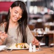 Stock Photo: Woman eating at a restaurant Woman eating at a restaurant