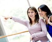 购物指向走购物妇女指着不远处的妇女 — 图库照片