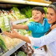 Woman at the supermarket with her son — Stock Photo #19778281