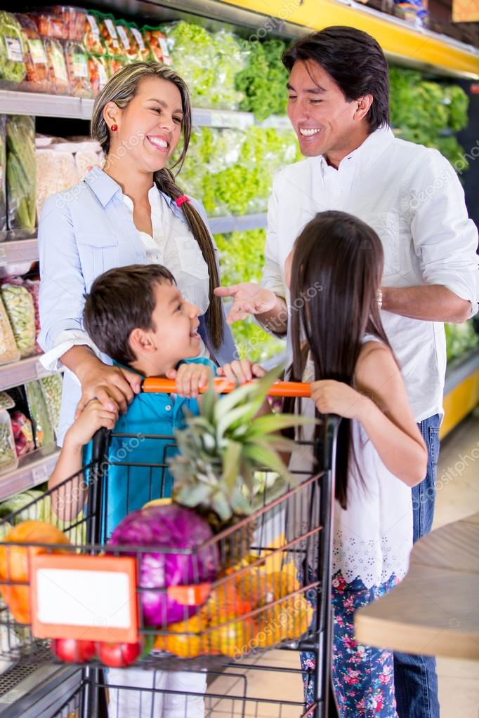 Happy family at the supermarket grocery shopping Happy family at the supermarket grocery shopping  — Stock Photo #19778371