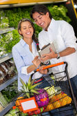 Couple with shopping list on a tablet Couple with shopping list on a tablet — Stock Photo