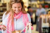 Woman looking into a shopping bag — Stockfoto