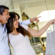 Happy couple pointing inside the store - Stock Photo