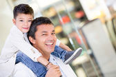 Dad carrying his son at the mall — Stock Photo