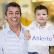 Man and son with an open sign — Stock Photo