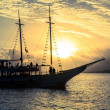 Boat sailing at sunset - Stock Photo