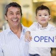 Dad and son holding open sign — Stock Photo #23654269