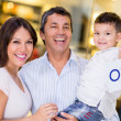 Family holding an open sign — Stock Photo #23654283