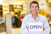 Business owner with an open sign — Foto de Stock