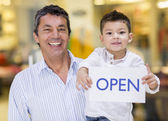 Dad and son holding an open sign — Stock Photo