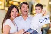 Family holding an open sign — Stock Photo