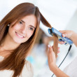 Stock Photo: Using hair straightener at salon